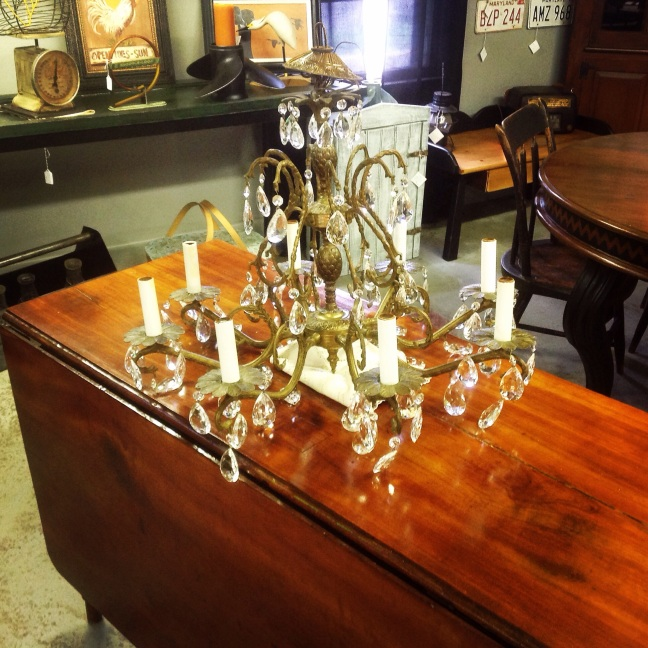 This vintage brass 8 arm chandelier would look great in any room. It is sitting on a beautiful drop leaf farm table.