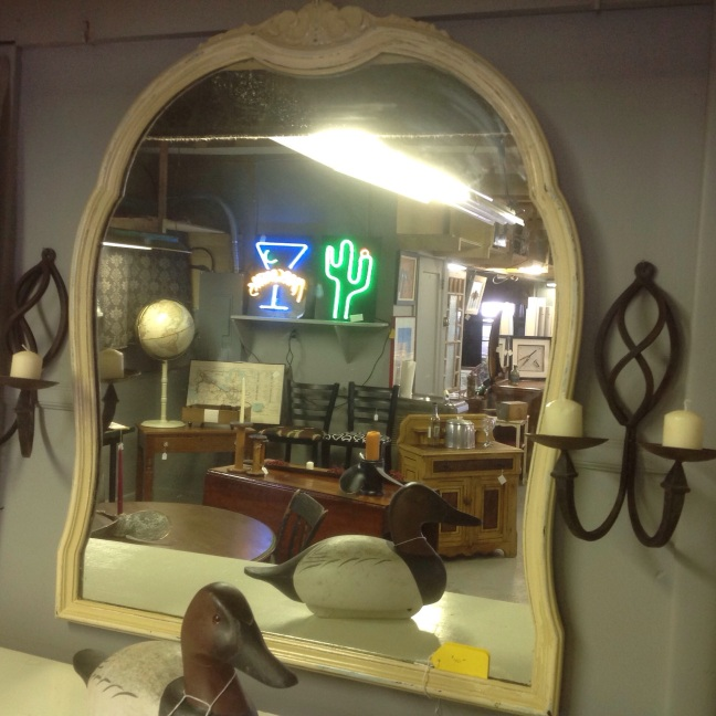 A pair of cast iron sconces beside a beautiful shabby chic mirror
